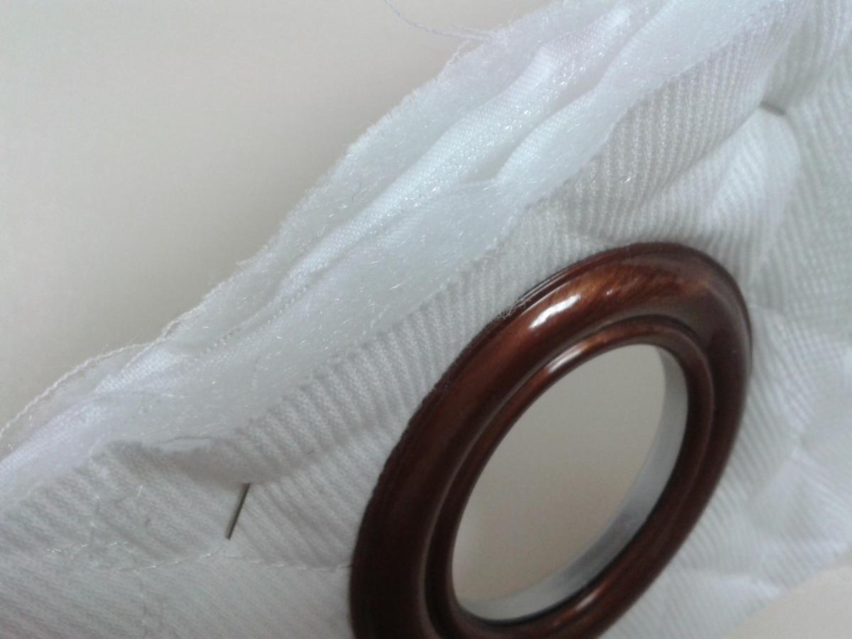 2 épaisseurs de tissu matelassé, la bande de renfort et l'oeillet clipsé